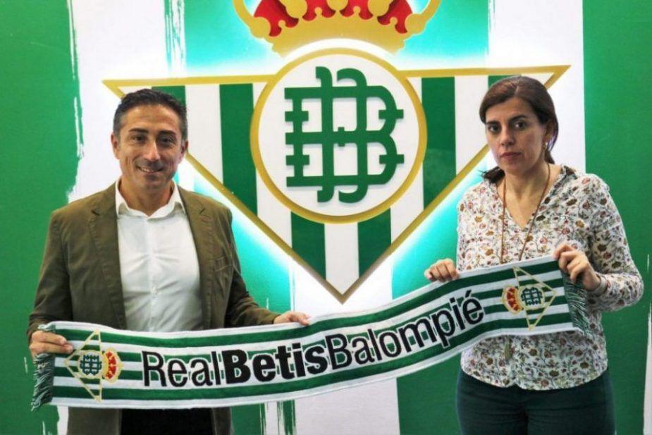 Antonio Contreras posa ante el escudo del Real Betis junto a María Victoria López